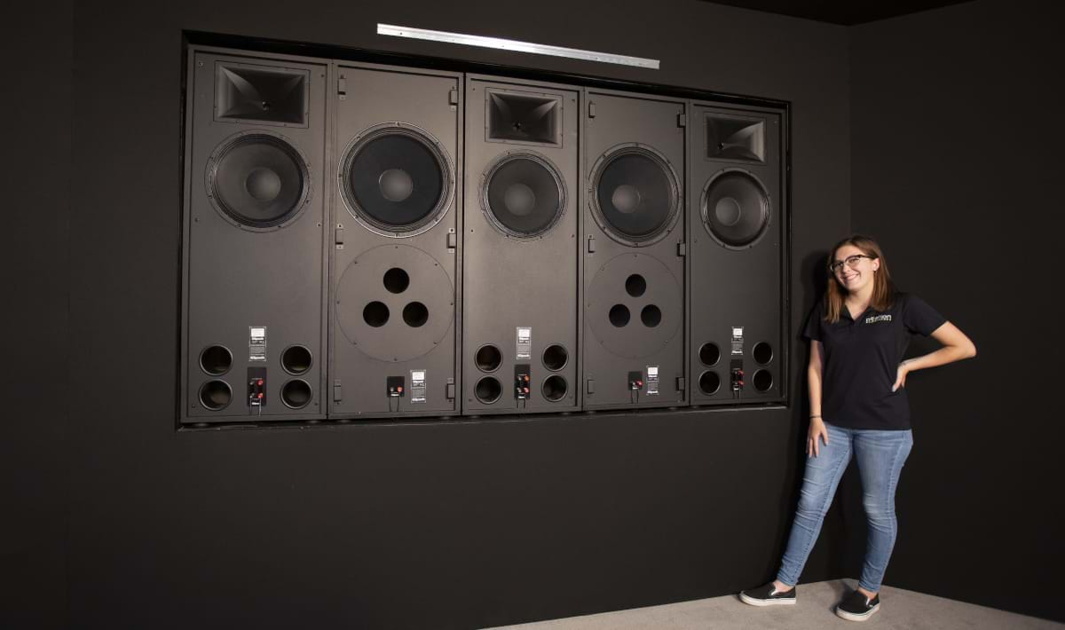 A women standing next to massive speakers that are use in home theater rooms