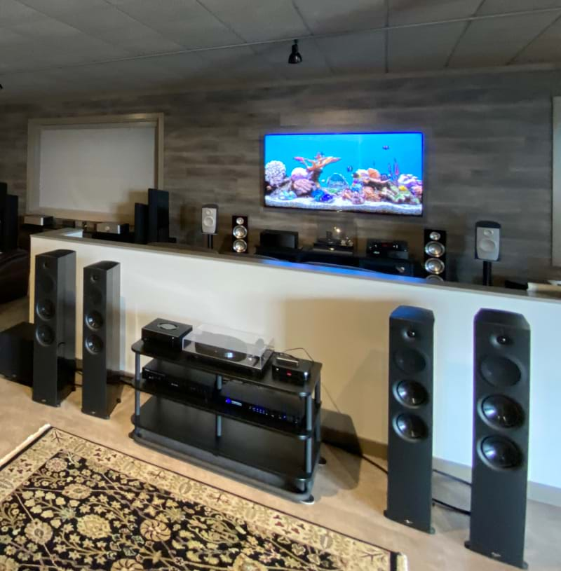 A a home theater setup, with musiplayers and multitude of speakers and a TV displaying an aquariam screen saver